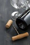 Botella de vino rojo, de vidrios y de sacacorchos en fondo de madera Fotografía de archivo libre de regalías