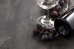 Botella de vino rojo, de vidrios y de uvas en un fondo de madera Imagenes de archivo