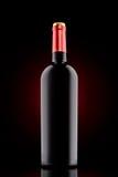 Botella de vino rojo en el fondo negro con el proyector rojo fotos de archivo libres de regalías