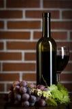 Botella de vino rojo en fondo de la pared de ladrillo Foto de archivo