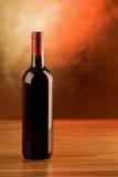 Botella de vino rojo en la tabla de madera y el fondo de oro Imágenes de archivo libres de regalías