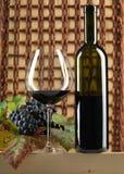 Botella de vino rojo, vidrio, uvas, fondo de mimbre Imágenes de archivo libres de regalías