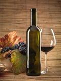 Botella de vino rojo, vidrio, uvas, fondo de mimbre Imagen de archivo