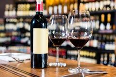 Botella de vino rojo y de dos vidrios Foto de archivo