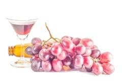 Botella de vino rojo, y de uvas Imagen de archivo