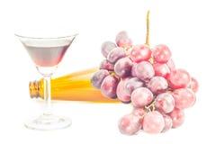 Botella de vino rojo, y de uvas en el fondo blanco Fotos de archivo