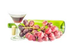 Botella de vino rojo, y de uvas en el fondo blanco Fotografía de archivo libre de regalías