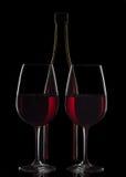 Botella de vino rojo y dos copas de vino en fondo negro Fotos de archivo libres de regalías