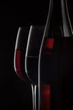 Botella de vino rojo y dos copas de vino en fondo negro Fotos de archivo