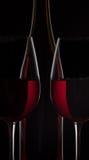 Botella de vino rojo y dos copas de vino en fondo negro Imagen de archivo libre de regalías