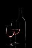 Botella de vino rojo y dos copas de vino en fondo negro en blac Imagen de archivo