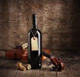 Botella de vino rojo y violín Foto de archivo libre de regalías