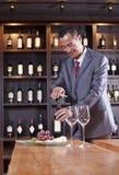 Botella de vino sonriente de la abertura del hombre de negocios en la tabla, estante con el vino en el fondo Foto de archivo