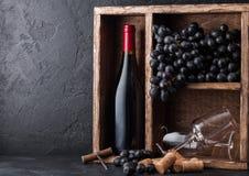 Botella de vino tinto y de vidrios vacíos con las uvas oscuras dentro de la caja de madera del vintage en fondo de piedra negro C foto de archivo