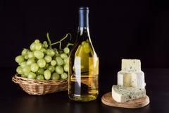 Botella de vino, uvas en una cesta de mimbre y queso verde Imagenes de archivo