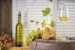 Botella de vino, vidrio de vino blanco con queso y uva Imagen de archivo