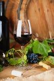 Botella de vino, vidrio, uvas y barril Imagenes de archivo