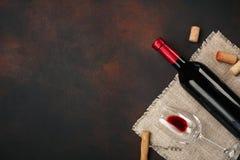Botella de vino, de vidrios, de sacacorchos y de corchos, en la opinión superior del fondo oxidado foto de archivo libre de regalías
