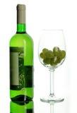 Botella de vino y copa con la uva Imagen de archivo