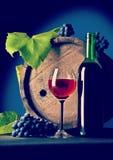 Botella de vino y de copa con la uva cerca del barrilete de madera del vintage Fotos de archivo