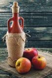 Botella de vino y de manzanas en un fondo del yute Imágenes de archivo libres de regalías