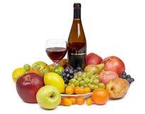Botella de vino y de vidrio rodeados por la fruta Fotos de archivo libres de regalías