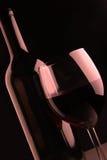 Botella de vino y vidrio footed Fotos de archivo libres de regalías