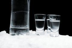 Botella de vodka con los vidrios que se colocan en el hielo en fondo negro Imágenes de archivo libres de regalías