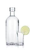 Botella de vodka y de vaso de medida con la rebanada de la cal Imagen de archivo libre de regalías