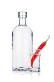 Botella de vodka y de vaso de medida con pimienta de chile rojo Imagenes de archivo