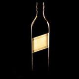 Botella de whisky en la oscuridad fotos de archivo