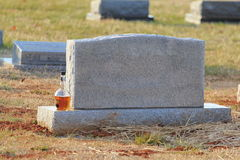 Botella de whisky por la piedra sepulcral en blanco Foto de archivo
