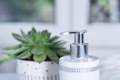 Botella decorativa del jabón líquido con zircons y planta verde en cuarto de baño Imágenes de archivo libres de regalías