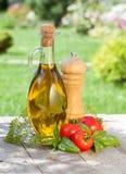 Botella del aceite de oliva, coctelera de la pimienta, tomates e hierbas Imagen de archivo