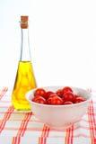 Botella del aceite de oliva y cereza roja de los tomates Imagen de archivo