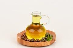 Botella del aceite de ricino con las frutas, las semillas y la hoja del echador imagen de archivo