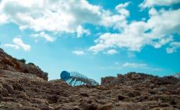 Botella del animal doméstico con agua en el arena de mar Imagenes de archivo