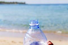 Botella del animal doméstico con agua en el arena de mar Foto de archivo libre de regalías