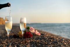 Botella del champán, dos vidrios en la playa Imagen de archivo libre de regalías