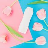 Botella del champú y flores de los tulipanes en fondo rosado y azul Endecha plana, visión superior Concepto de la belleza fotografía de archivo