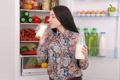 Botella del control de la chica joven de leche, colocándose cerca del refrigerador abierto foto de archivo libre de regalías
