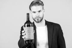 Botella del control del hombre de vino, alcohol Machista con la botella, malos hábitos Sommelier o degustator con el vino, lagar  imagen de archivo libre de regalías