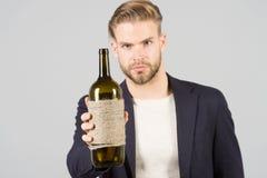 Botella del control del hombre de vino, alcohol Machista con la botella, malos hábitos Sommelier o degustator con el vino, lagar  imágenes de archivo libres de regalías