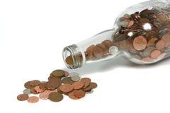 Botella del dinero que derrama monedas Imagenes de archivo