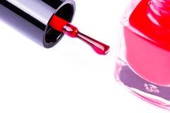 Botella del esmalte de uñas de la moda y cepillo rojos del clavo en el fondo blanco Imágenes de archivo libres de regalías