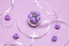 Botella del espray de perfume con las pequeñas rosas de la lila y la cinta blanca Fragancia como regalo para la mujer imágenes de archivo libres de regalías