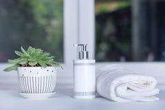 Botella del jabón líquido, toalla blanca y planta verde en cuarto de baño Foto de archivo libre de regalías