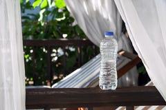 Botella del plástico transparente con agua que se coloca en una terraza Fotografía de archivo libre de regalías