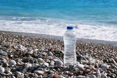 Botella del plástico transparente con el agua potable que se coloca en la playa con una opinión del mar Fotografía de archivo libre de regalías