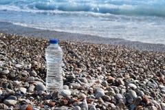 Botella del plástico transparente de agua en la playa con una opinión del mar Imagen de archivo libre de regalías